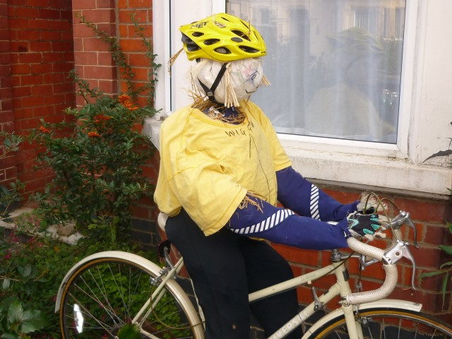 Cycling scarecrow being displayed in a garden.