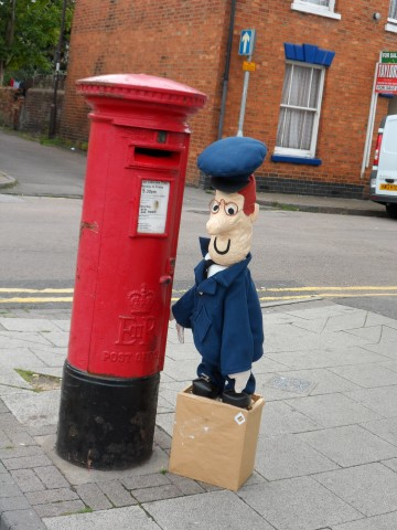 Postman Pat scarecrow next to a postbox in Wolverton Square.