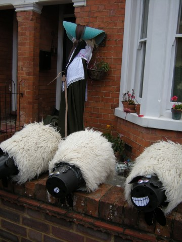 Sheep scarecrows in a garden.