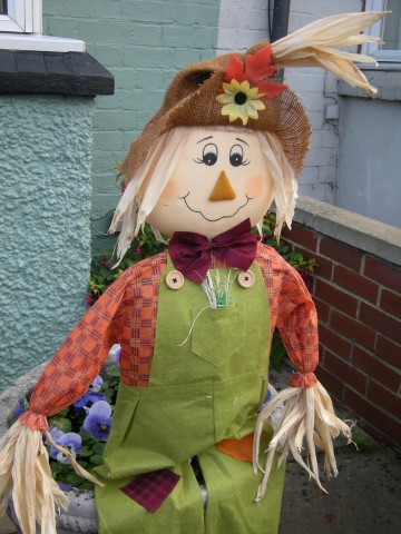 Happy scarecrow sitting on a plant pot.