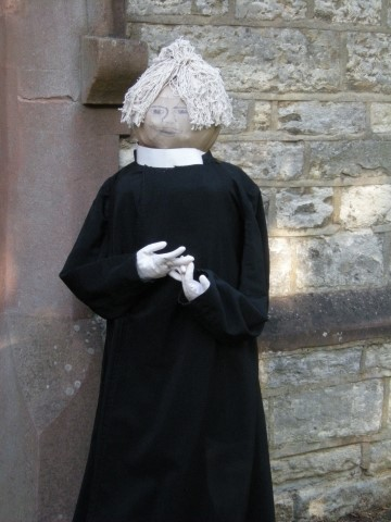 A priest scarecrow outside of the Church.
